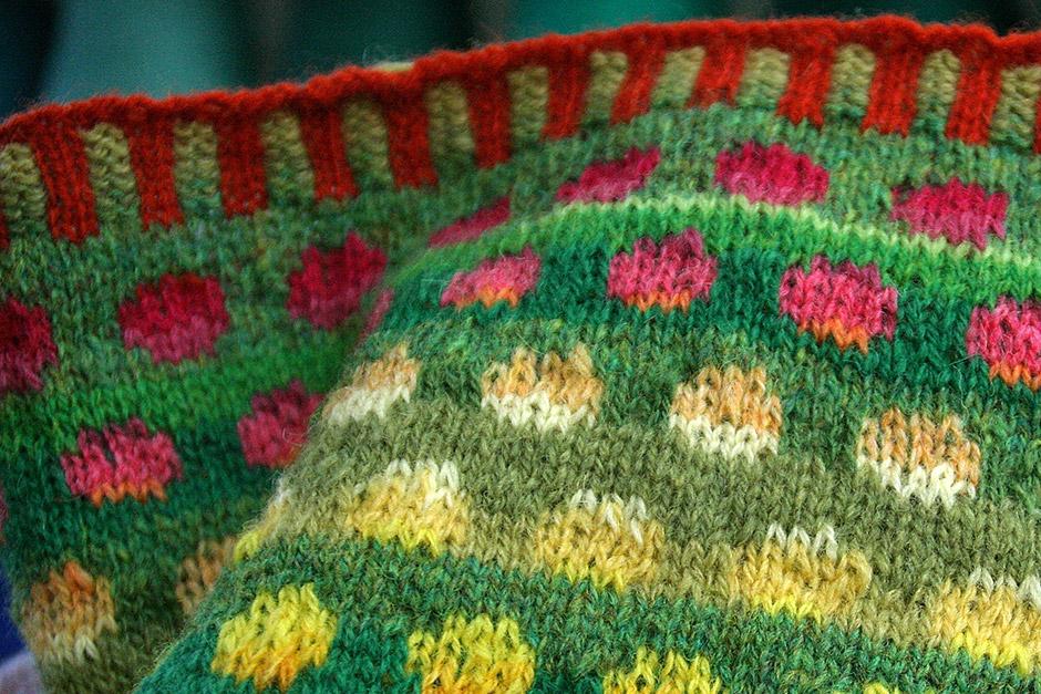 Schal mit bonbonfarbenem Einstrickmuster und grünem Hintergrund.